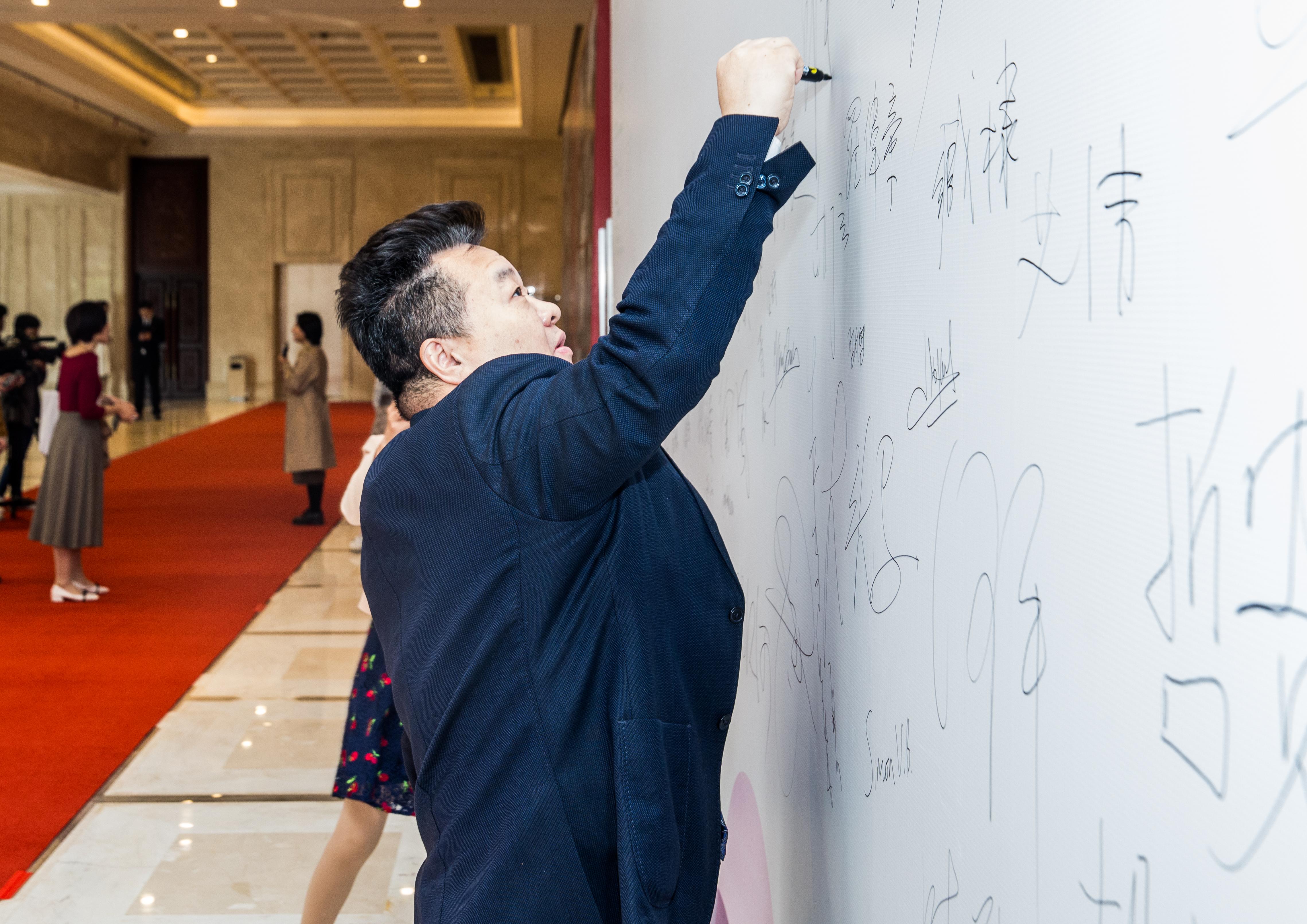 邱華棟在簽名墻上簽字